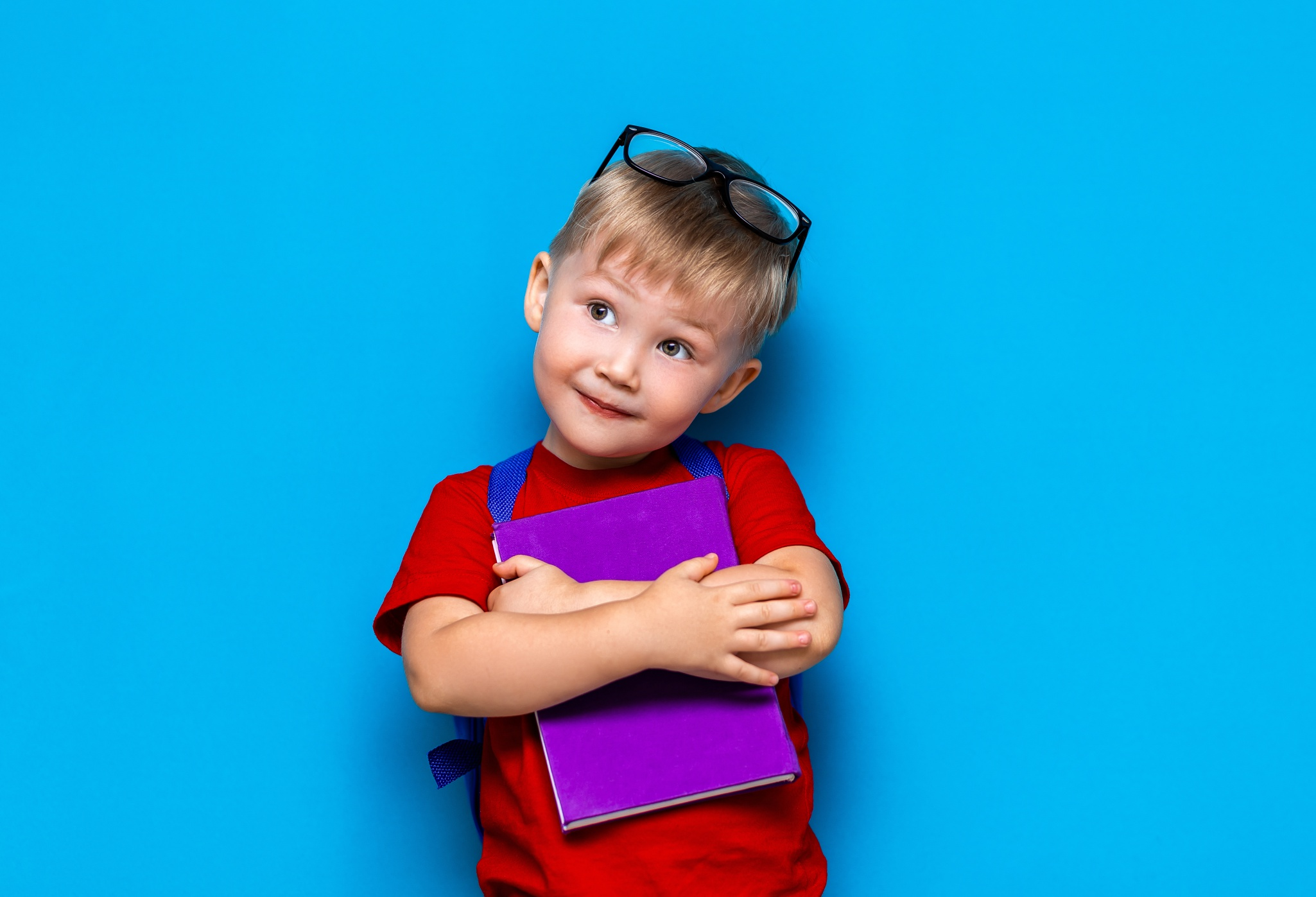 Small Happy Smiling Boy With Glasses On His Head, Book In Hands, Schoolbag On His Shoulders. Back To School. Ready To School